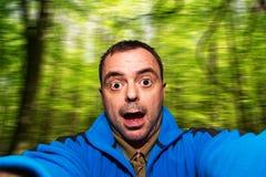 Équipez le selfie parlant tirant le visage drôle sur le fond brouillé image libre de droits