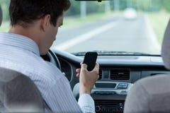Équipez le service de mini-messages au téléphone portable pendant conduire une voiture Photographie stock