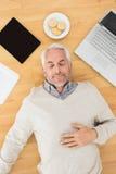Équipez le sommeil avec l'électronique et les biscuits sur le plancher de parquet Images stock