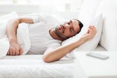 Équipez le sommeil dans le lit avec le smartphone sur le nightstand photo libre de droits