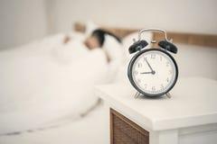 Équipez le sommeil sur le lit dans la chambre à coucher et le réveil photographie stock libre de droits