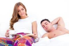 Équipez le sommeil tandis que son amie lit dans le lit Photographie stock libre de droits