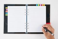 Équipez le stylo de participation de main et le carnet d'écriture sur le fond blanc f Photographie stock