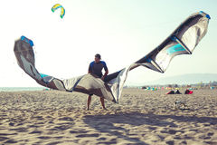 Équipez le surfer professionnel se tenant dans le wetsuit avec son cerf-volant Photos stock