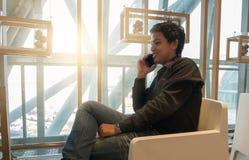 Équipez le téléphone intelligent d'utilisation dans le salon d'aéroport dans le temps de matin Photos stock