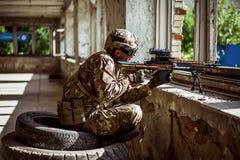 Équipez le tireur isolé avec l'arme automatique avec une vue télescopique images stock
