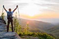 Équipez le touriste avec des poteaux de trekking sur la colline au lever de soleil Photographie stock