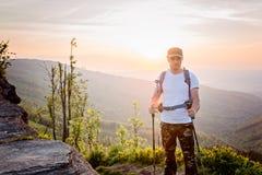 Équipez le touriste avec des poteaux de trekking sur la colline au lever de soleil Photos libres de droits
