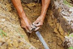 Équipez le travail avec des tuyaux en terre tout en installant un nouveau système d'arrosage souterrain photos stock
