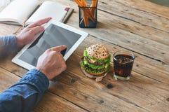 Équipez le travail avec une tablette à une table en bois Images libres de droits