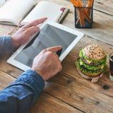 Équipez le travail avec une tablette à une table en bois Photo libre de droits