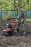 Équipez le travail dans le jardin préparant le cultivateur moulu Photo libre de droits