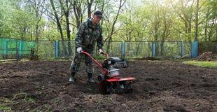 Équipez le travail dans le jardin préparant le cultivateur moulu Image libre de droits