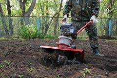 Équipez le travail dans le jardin préparant le cultivateur moulu Photos stock