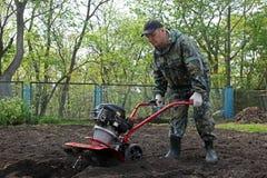 Équipez le travail dans le jardin préparant le cultivateur moulu Photographie stock
