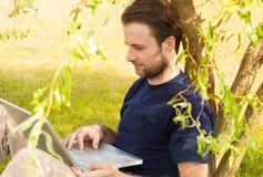 Équipez le travail sur l'ordinateur portable extérieur en parc photos stock