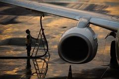 Équipez le travailleur alimentant l'avion à l'aéroport Photo stock