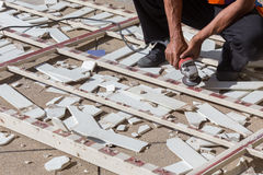 Équipez le travailleur réparant la barrière en acier avec la scie électrique Photo libre de droits