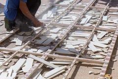 Équipez le travailleur réparant la barrière en acier avec la scie électrique Photos libres de droits