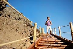 Équipez le trekking sur les escaliers en bois le long d'un chemin rocheux Image libre de droits