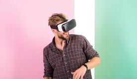 Équipez le type non rasé avec des verres de VR, fond rose Appréciez la réalité virtuelle Technologies modernes d'utilisation de h photographie stock