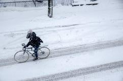 Équipez le vélo d'équitation sur Rachel Street pendant la tempête de neige Photo libre de droits