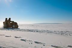 Équipez le vélo de quadruple d'équitation sur le champ neigeux d'hiver Images stock