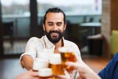 Équipez le verre de bière tintant avec des amis au restaurant Photo stock