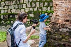 Équipez le videographer et ses pousses de fils visuels dans le stabilisateur électronique, steadycam pour tirer au Cham Tovers de Image libre de droits