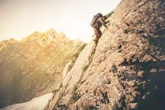 Équipez le voyageur avec le grand sac à dos s'élevant sur des roches Images libres de droits