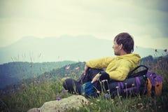 Équipez le voyageur avec le sac à dos détendant avec des montagnes sur le fond photo stock