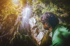 Équipez le voyageur détendant avec la vue de cascade en montagnes Photo stock