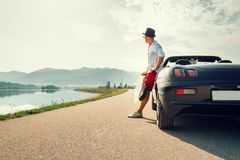 Équipez le voyageur solo sur le repos de voiture de cabriolet sur la montagne pittoresque images stock