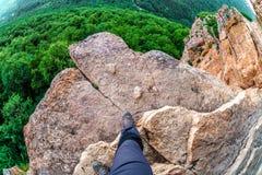 Équipez les étapes de randonneur sur le bord de la roche de montagne au-dessus du précipice avec les arbres forestiers verts dess photo libre de droits