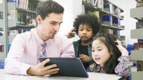 Équipez les étudiants de professeur et d'enfant apprenant et regardant sur le devi de comprimé photographie stock libre de droits