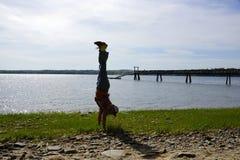 Équipez les appuis renversés sur la plage herbeuse rocheuse avec le pilier Image stock