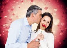 Équipez les baisers sur des joues de femme tout en tenant la rose de rouge Image libre de droits