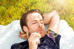 Équipez les bulles de savon de soufflement tout en s'étendante extérieure sur l'herbe Photographie stock