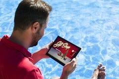 Équipez les cadeaux de Noël d'achats par l'Internet avec un comprimé électronique tout en se reposant sur le poolside Images stock