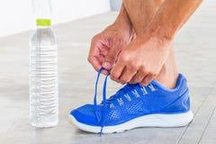 Équipez les chaussures de sport de laçage dans le gymnase avec la bouteille d'eau image libre de droits