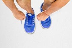 Équipez les chaussures de sport de laçage sur le plancher blanc dans la forme physique, exercice de sport photographie stock