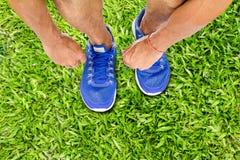 Équipez les chaussures de sport de laçage sur le plancher d'herbe verte, concept d'exercice de sport image libre de droits