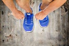 Équipez les chaussures de sport de laçage sur le plancher en béton de vieux vintage, exercice de sport image libre de droits