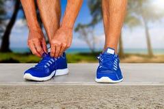 Équipez les chaussures de sport de laçage sur le fond brouillé de plage avec la lumière du soleil douce photographie stock libre de droits