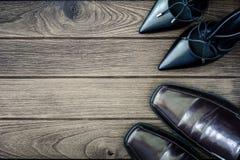 équipez les chaussures noires de chaussures et de talons hauts de femme sur le backg en bois brun Photographie stock