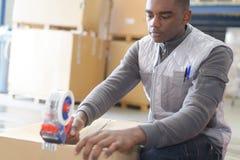 Équipez les colis d'emballage avec la bande collante à l'entrepôt photo libre de droits