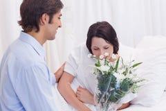 Équipez les fleurs portées à son amie dans l'hôpital Photo libre de droits