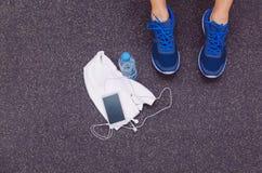 Équipez les jambes avec des espadrilles, serviette, l'eau et Photographie stock