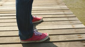 Équipez les jambes du ` s portant des jeans et des chaussures rouges de tissu sur le dock en bois - en se tenant au soleil Images libres de droits
