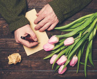 Équipez les mains écrivant sur des feuilles de papier blanc sur le vieux bunc en bois de table Images stock